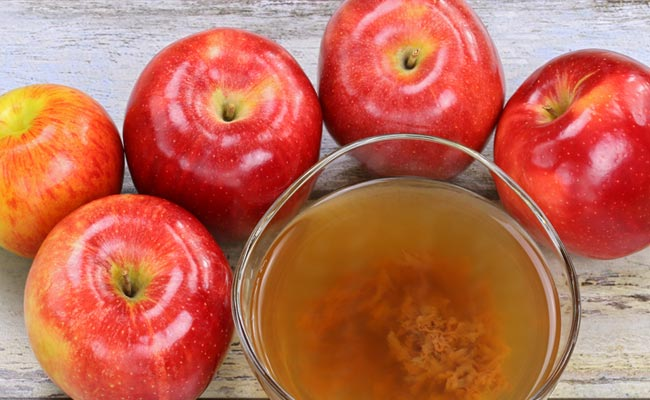 image of a bowl of apple cider vinegar with 5 apples