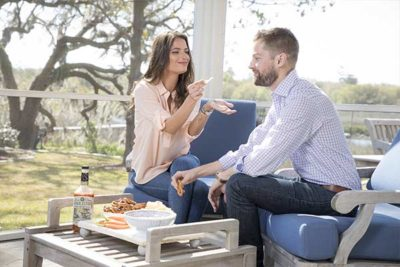 Two people sitting on chairs and eating snacks