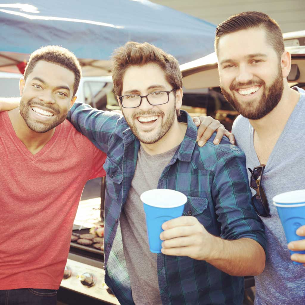 3 men smiling and holding drinks
